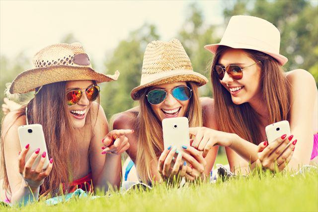 スマホ画面を見る3人の女性